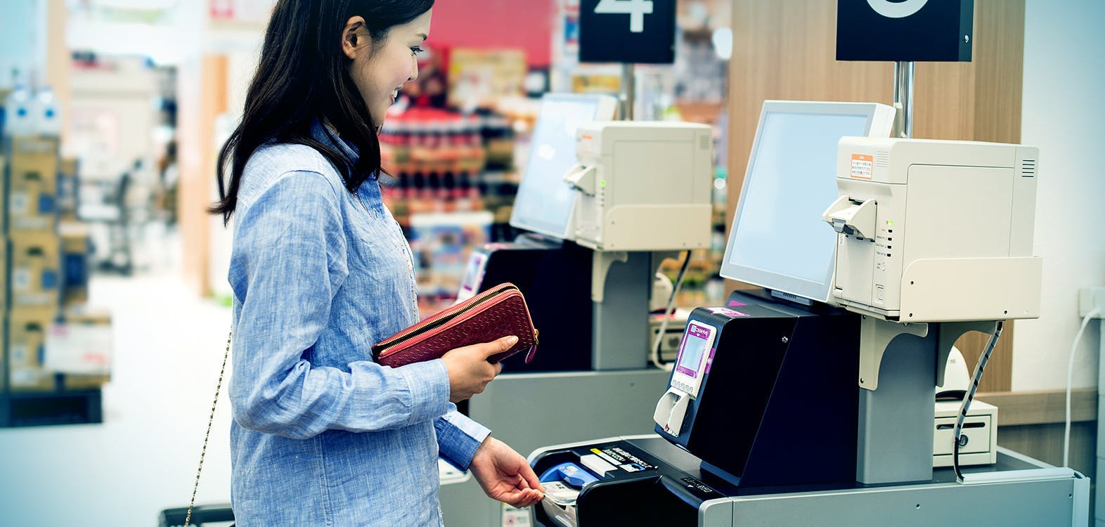 woman getting cash from a self checkout
